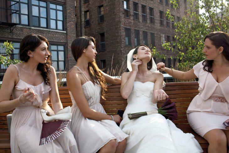 Novia sentada en una banca junto a sus damas de honor