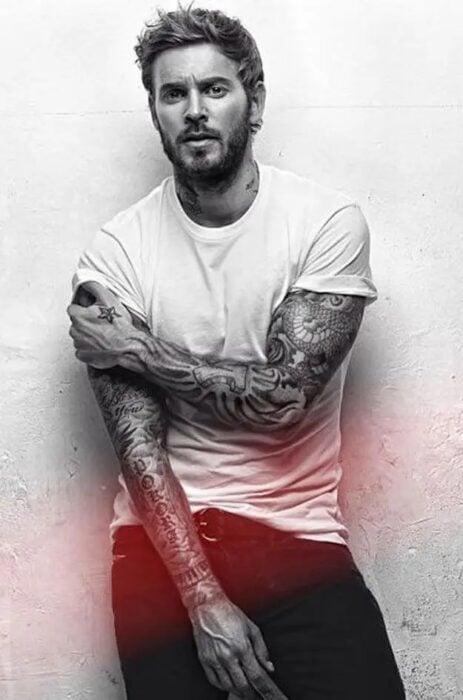 Chic cubierto de tatuajes en los brazos recargado en una pared mientras le toman una fotografía
