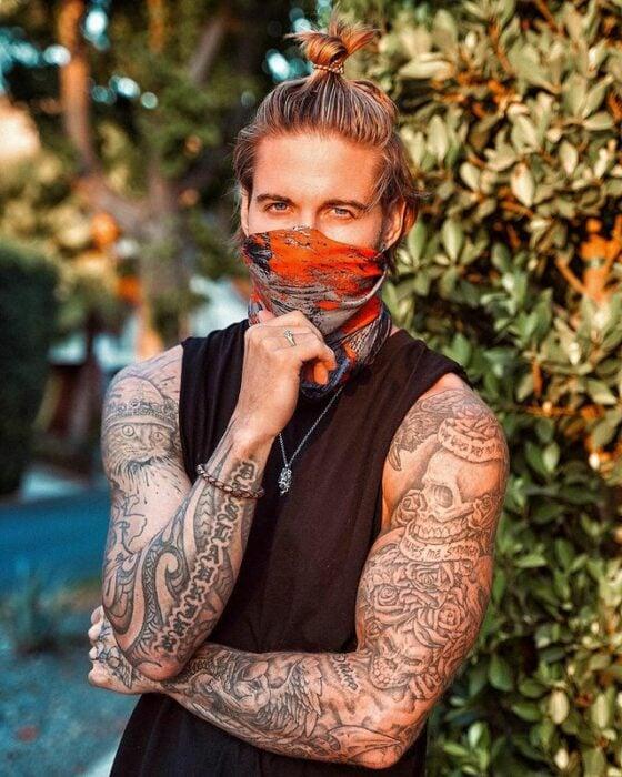 Chico con tatuajes usando una mascarill