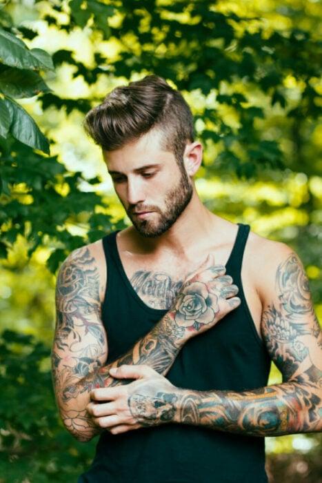 Chico con tatuajes pensando mientras está en un jardín