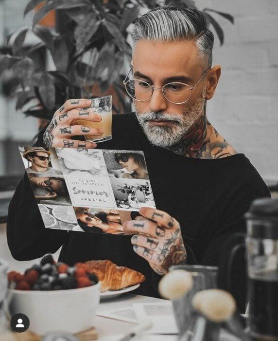 Hombre con tatuajes tomando un desayuno mientras lee una revista