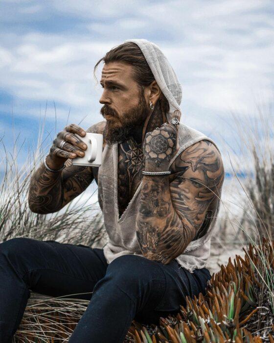 Hombre tatuado tomando una taza de café mientras está admirando el paisaje
