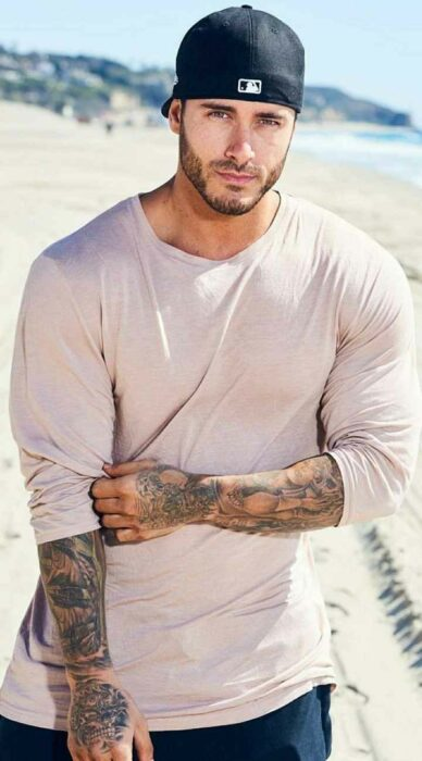 Hombre tatuado usando una camiseta 3/4 mostrando sus tatuajes