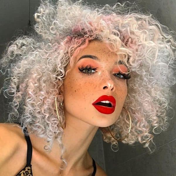 Chica con el cabello rizado y teñido de color platinado con la raíz rosa