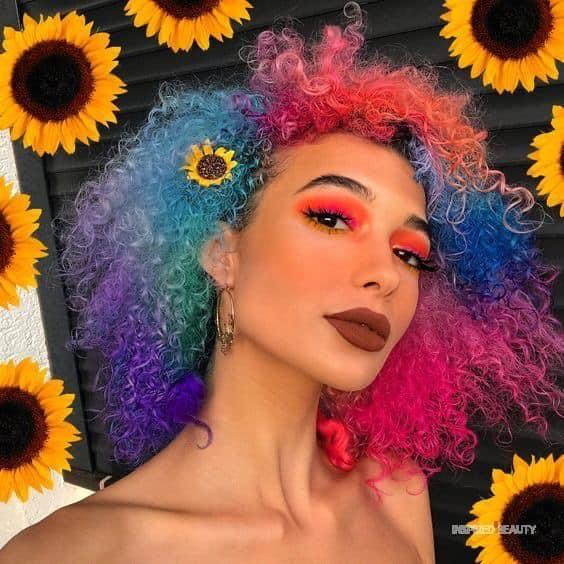 Chica con el cabello rizado y teñido de colores