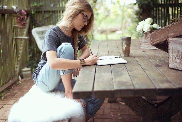 Chica sentada en una banca escribiendo sobre un papel; Las personas con 'letra fea' son más inteligentes que el resto estudio