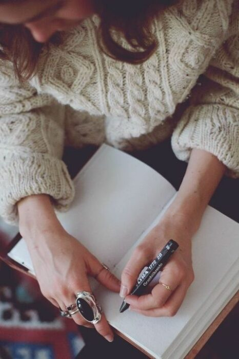 Chica escribiendo sobre una libreta; Las personas con 'letra fea' son más inteligentes que el resto estudio