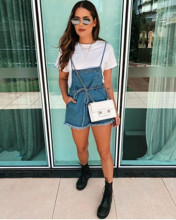 Girl wearing overalls with a white blouse