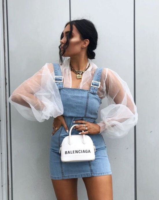 Girl wearing overalls with a white blouse with transparencies