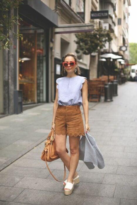 Chica usando shorts con sandalias de plataforma y blusa blanca