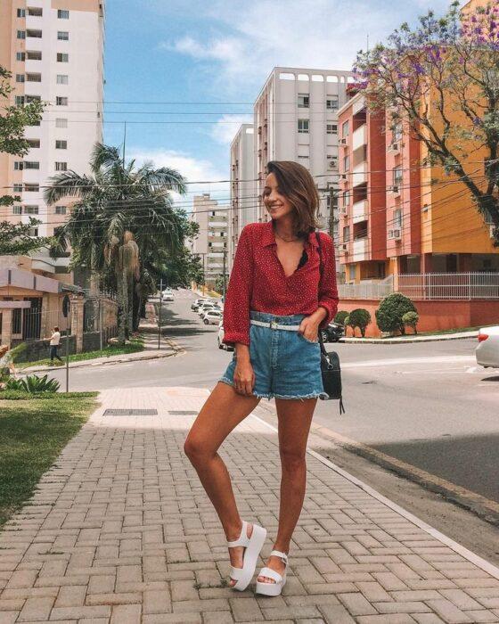 Chica usando shorts de mezclilla, blusa roja y sandalias de plataforma