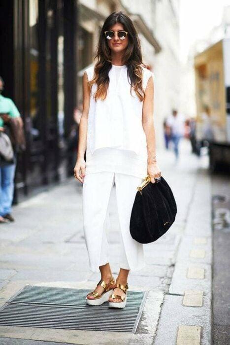 Chica usando un look total white con sandalias de color dorado