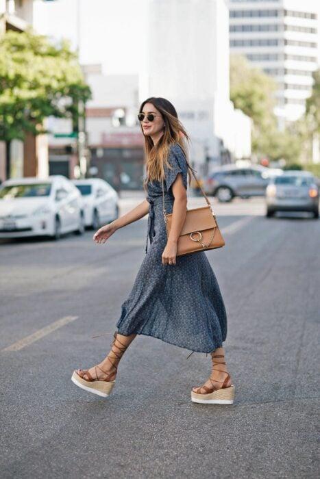 Chica caminando por la calle mientras usa un vestido y sandalias de plataforma