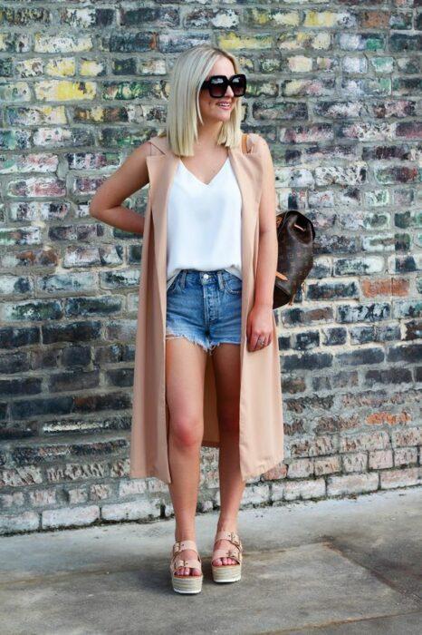 Chica usando un short, chaleco largo y blusa blanca con sandalias de plataforma
