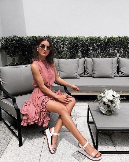 Chica sentada en una sala usando un vestido rosa con sandalias de plataforma