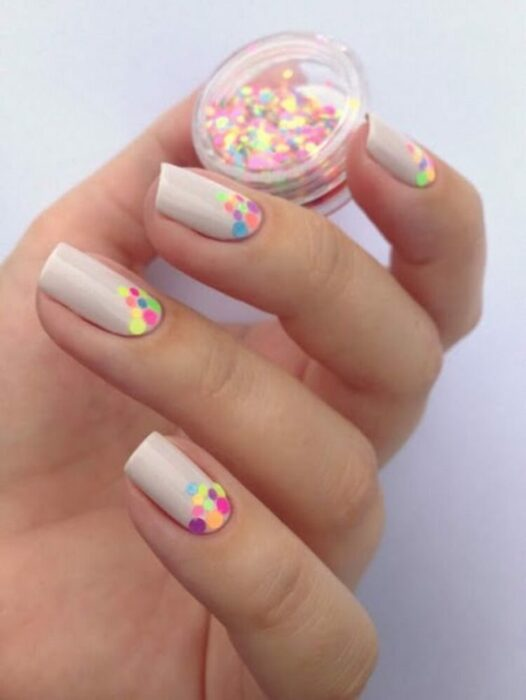 Manicura en tono nude con puntos fluorescentes; Manicuras con puntitos de colores