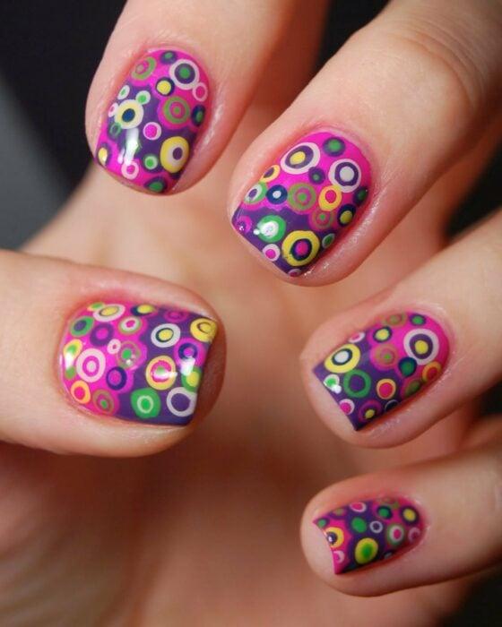 Manicura en fondo rosa con puntos psicodélicos;  Manicuras con puntitos de colores