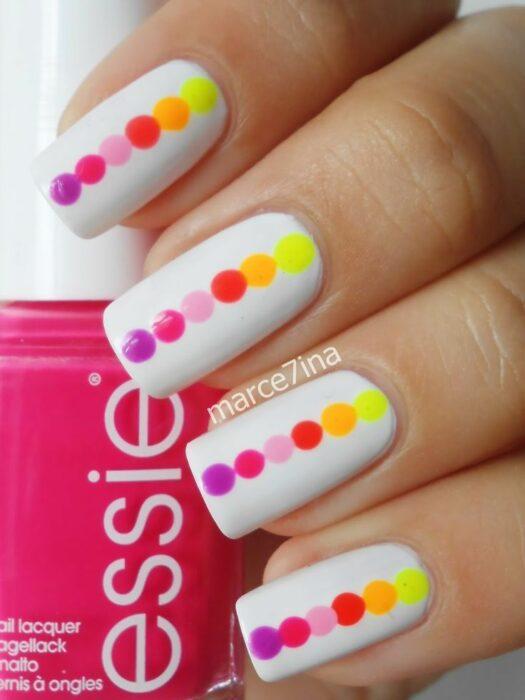 Manucira en tono nude con puntos fluorescentes; Manicuras con puntitos de colores
