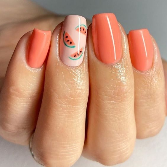 Peach colored manicure decorated with watermelon stickers