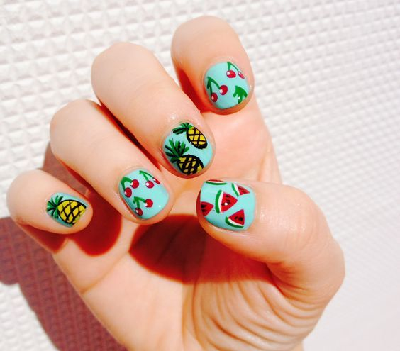 Manicure with aqua blue background decorated with tropical fruits; Fruity manicures to spice up your spring