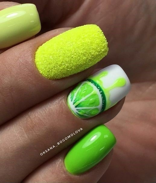 Manicure in green tone decorated with half a lemon in fluorescent tone