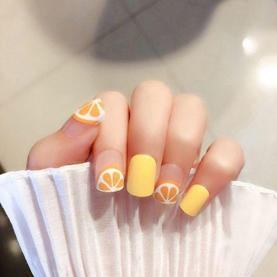 Manicura en color amarillo con rodajas de naranjas; Manicuras frutales para darle sabor a tu primavera