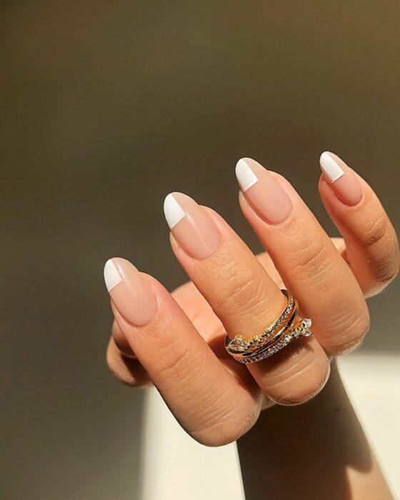 Chica con las uñas pintadas en tonos nude con blanco