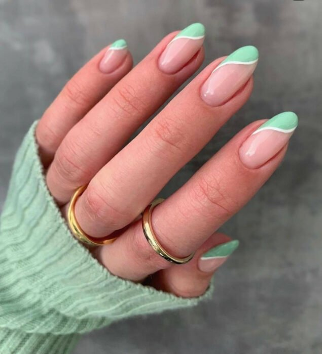 Girl with nails painted in nude tones with mint lines