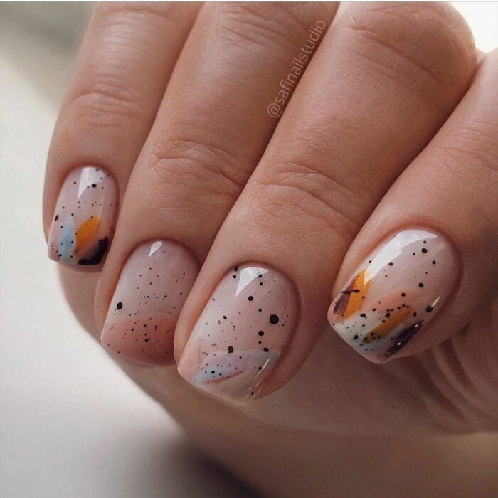 Girl with nails painted in nude tones with colors