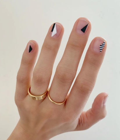 Girl with nails painted in nude tones with black and white lines