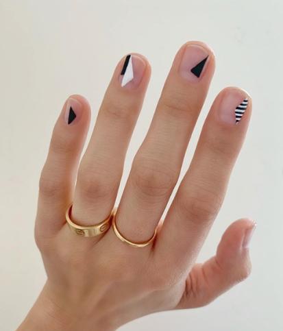 Chica con las uñas pintadas en tonos nude con líneas blanco y negro