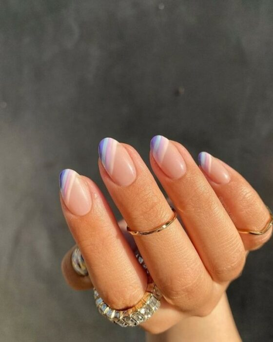 Girl with nails painted in nude tones with a mixture of pink and lilac