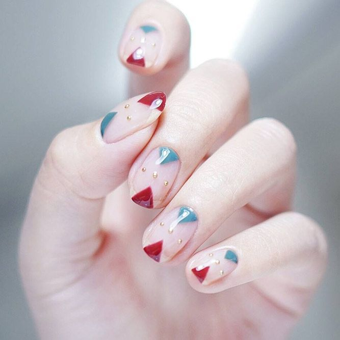 Girl with nails painted in nude tones and a mixture of red and blue tones