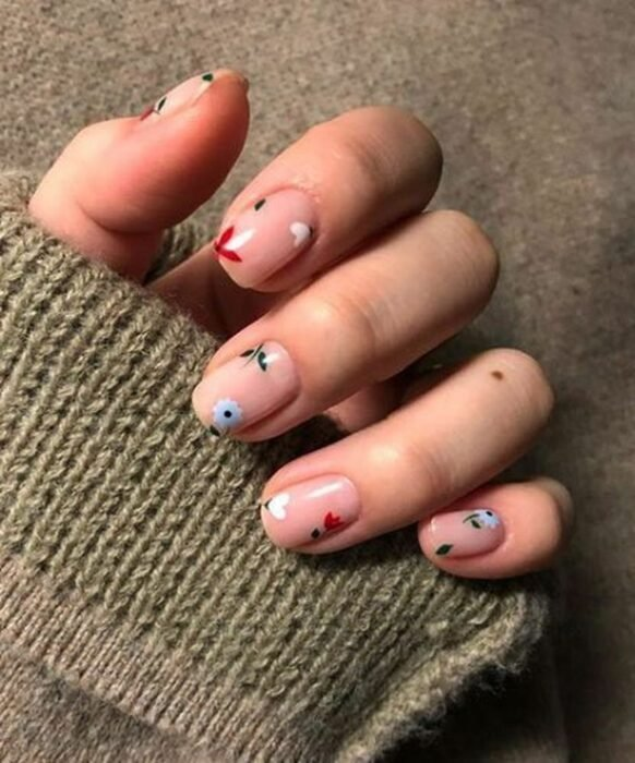 Girl with nails painted in nude tones with flowers