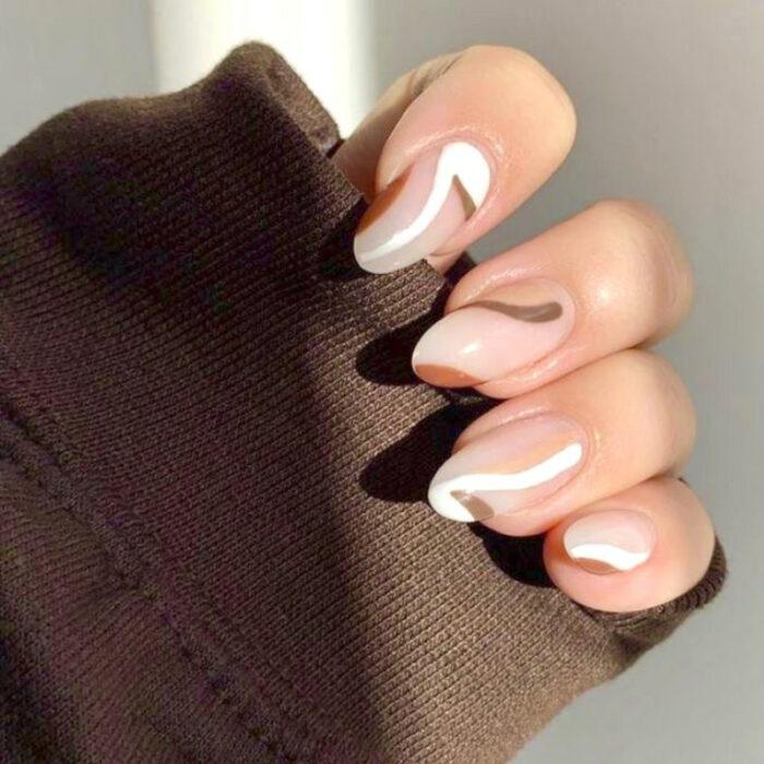 Chica con las uñas pintadas en tonos nude y líneas blancas