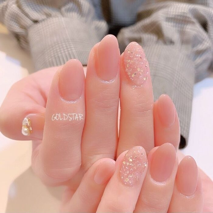 Girl with nails painted in nude tones with a touch of gold