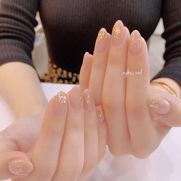 Girl with nails painted in nude tones