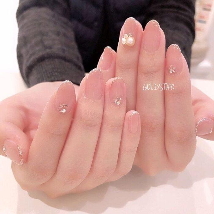 Chica con las uñas pintadas en tonos nude con perlas