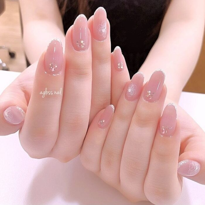 Girl with nails painted in nude rhinestones