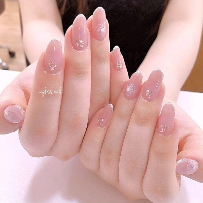 Chica con las uñas pintadas en tonos nude pedrería