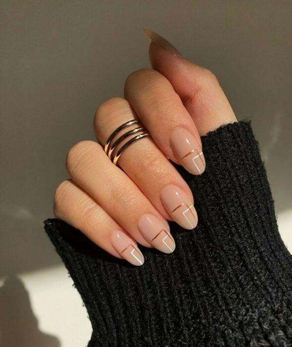 Chica con las uñas pintadas en tonos nude con líneas blancas y café
