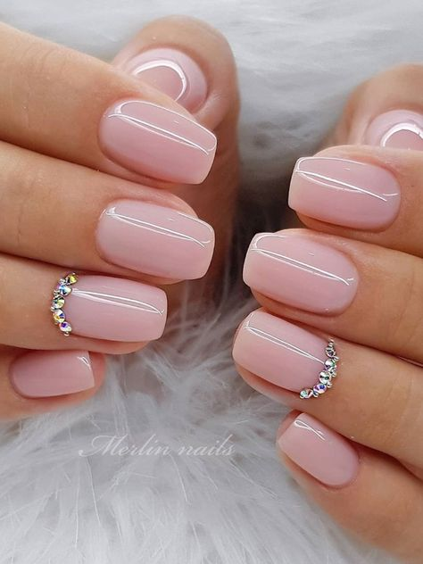 Girl with nails painted in nude tones with stones