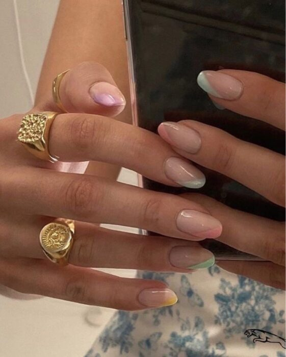 Girl with nails painted in nude tones with colored tips