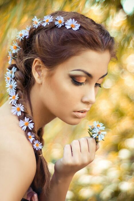 Girl in profile with daisies between her braids; Spring makeup you'll love