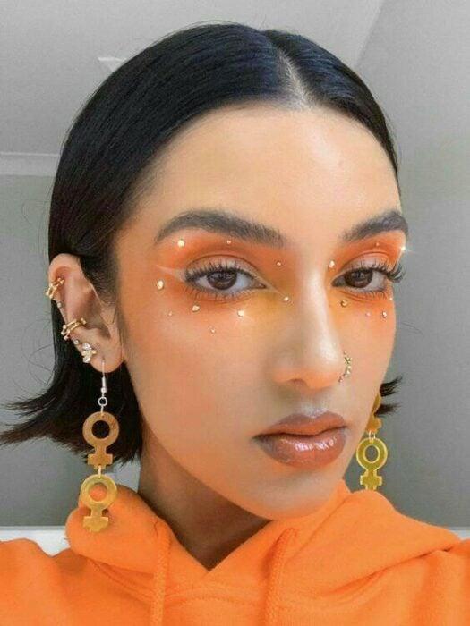chica con maquillaje naranja con perlas en ojos; 13 Maquillajes aesthetic para presumir en tu IG