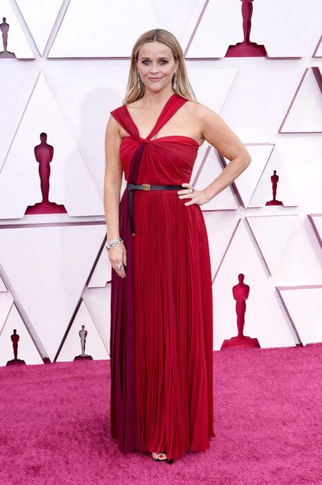 Reese Witherspoon en la alfombra roja de los oscar usando un vestido de color rojo quemado