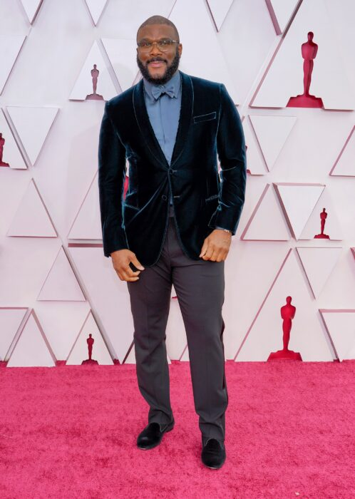 Tyker Perry usando un saco de terciopelo con camisa azul y un pantalón de color gris en la entrega de premios Óscar 2021