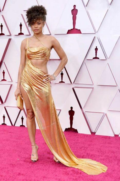 Andra Day en la alfombra roja de los oscar usando un vestido de color dorado