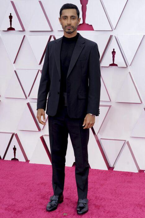 Riz Ahmed en la alfombra roja de los oscar usando un traje de color negro