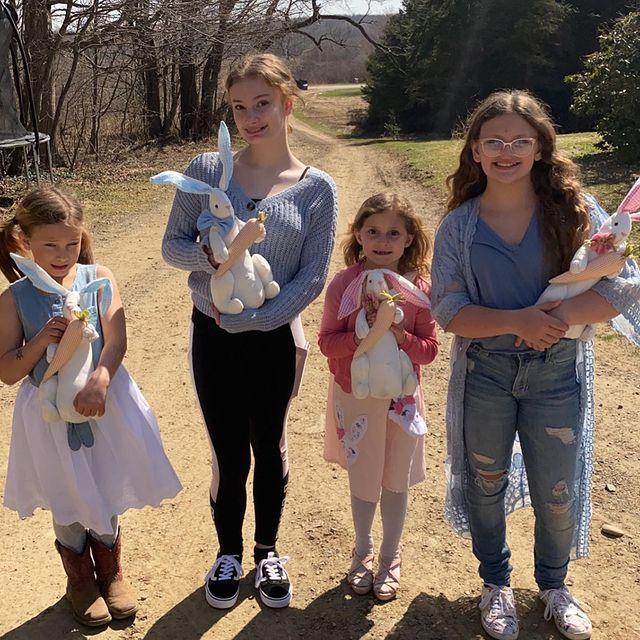 Niñas en un terreno cargando conejos de pascua con dulces